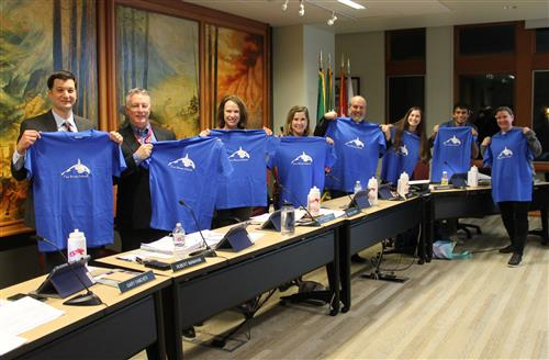 School Board Directors model t-shirts with the new Two Rivers logo.